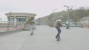 Парни конька выполняя фокусы и навыки на улице
