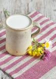 Парное молоко в керамических кружке и цветках Стоковые Изображения RF