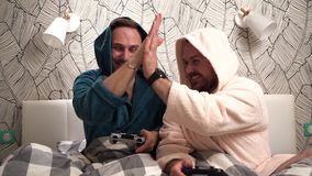 2 парня играют компютерные игры на кровати в купальных халатах и выигрыше Отснятый видеоматериал замедленного движения 2 бородаты акции видеоматериалы