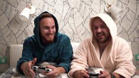 2 парня играют компютерные игры на кровати в купальных халатах и выигрыше Отснятый видеоматериал замедленного движения 2 бородаты видеоматериал