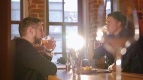 2 парня сидя на таблице в пиве ресторана, веселить и выпивать видеоматериал
