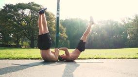 2 парня фитнеса делая подбрюшные тренировки видеоматериал