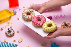 партия Вручите держать плиту донута красочного слащавого круга застекленного стоковая фотография rf