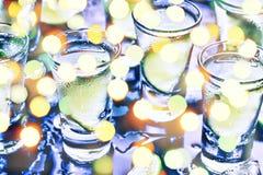 Партия в клубе Коктеили на баре Спирт Водочка, джин, текила с льдом и известка Спиртной коктеиль коктеиля селективно стоковое изображение rf