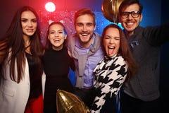 Партия Нового Года, праздники, торжество, ночная жизнь и концепция людей - молодые люди имея танцы потехи на партии Стоковое фото RF