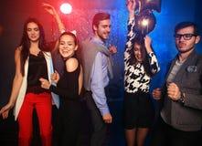 Партия Нового Года, праздники, торжество, ночная жизнь и концепция людей - молодые люди имея танцы потехи на партии Стоковое Изображение RF