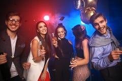 Партия Нового Года, праздники, торжество, ночная жизнь и концепция людей - молодые люди имея танцы потехи на партии стоковое изображение