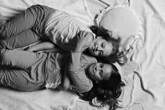 Партия пижамы и концепция детства Девушки лежат на белый и розовый обнимать простынь стоковая фотография rf
