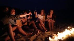 Партия пляжа на заходе солнца с костром Друзья сидя вокруг костра, выпивая пиво и поя к гитаре Молодые сток-видео