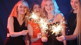 Партия, праздники, ночная жизнь и счастливая концепция Нового Года - группа в составе счастливые женщины имея потеху с бенгальски сток-видео