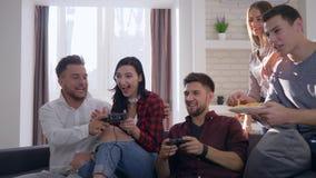 Партия хипстера молодости, эмоциональная компания друзей мальчиков и девушки имеют потеху и играют видеоигры акции видеоматериалы