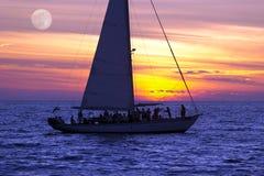 Партия людей фантазии океана луны захода солнца плавания парусника Стоковое фото RF