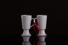 Партнерство и концепция поддержки 2 белых чашки на сподвижнице Стоковые Изображения