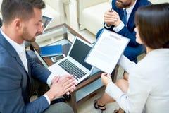 Партнеры обсуждая контракт дела в встрече Стоковое Изображение RF