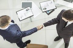 Партнеры рукопожатия финансовые, на предпосылке настольного компьютера, с финансовыми план-графиками Стоковые Фото