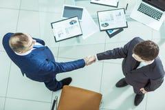 Партнеры рукопожатия финансовые, на предпосылке настольного компьютера, с финансовыми план-графиками Стоковое Фото