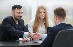 Партнеры рукопожатия финансовые сидя на таблице Стоковое фото RF