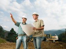 Партнеры смотря светокопию на строительной площадке Стоковая Фотография
