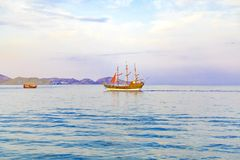 Парусник с ветрилами шарлаха на море идет к берегу стоковое фото