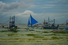 Парусник с голубым ветрилом на предпосылке облаков, острове Boracay, Филиппинах Стоковое Изображение RF