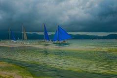 Парусник с голубым ветрилом на предпосылке облаков, острове Boracay, Филиппинах Стоковая Фотография