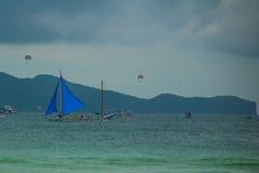 Парусник с голубым ветрилом на предпосылке облаков, острове Boracay, Филиппинах Стоковые Изображения RF
