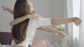 Пары азиатских женщин лесбосские счастливые просыпая вверх в утре Азиатские девушки сидя на кровати протягивая в уютной спальне д сток-видео