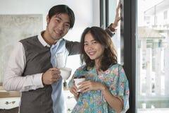 Пары азиатских молодого человека и женщины с кофейной чашкой в sta руки Стоковое Фото