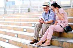 Пары азиатского туриста старика и женщины смотрят планшет и действующ как получите некоторые хорошие новости Это фото также содер стоковые фото