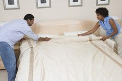 Пары аранжируя их кровать дома стоковые изображения