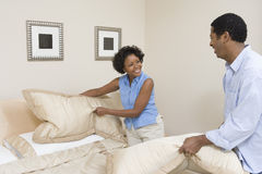 Пары аранжируя подушки на кровати стоковые изображения rf