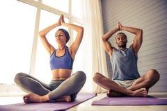 Пары Афро американские делая йогу Стоковые Изображения
