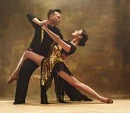 Пары бального зала танца в золоте одевают танцы на предпосылке студии стоковые фотографии rf