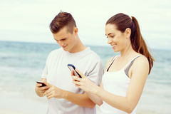 Пары бегунов с передвижными умными телефонами outdoors Стоковое фото RF
