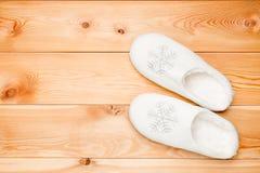 Пары белых теплых тапочек с снежинками осматривают сверху на a Стоковые Фото