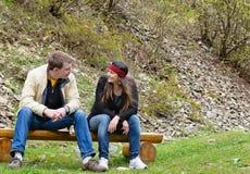 Пары беседуя outdoors сидеть дальше Стоковое Изображение RF