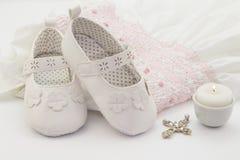 Пары белых ботинок младенца на вышитом крестя белом платье, Стоковое Изображение RF