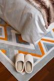 Пары белых тапочек на ковре около кровати Стоковые Фотографии RF