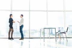 Пары бизнесмена, беседа женщины о инструменте объекта документа в комнате офиса против окна голубого неба с домами Стоковое фото RF