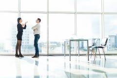 Пары бизнесмена, беседа женщины о инструменте объекта документа в комнате офиса против окна голубого неба с домами Стоковая Фотография