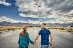 Пары битника идя на дорогу стоковая фотография