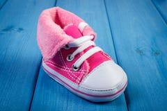 Пары ботинка младенца на голубых досках, предпологая для младенца Стоковая Фотография