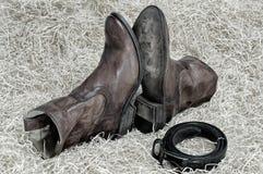Пары ботинок ковбоя и кожаного пояса на соломе Стоковое Изображение