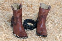 Пары ботинок ковбоя и кожаного пояса на соломе Стоковые Изображения RF