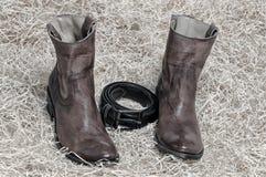Пары ботинок ковбоя и кожаного пояса на соломе Стоковые Фото