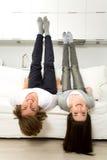 Пары вверх ногами на софе Стоковые Фотографии RF