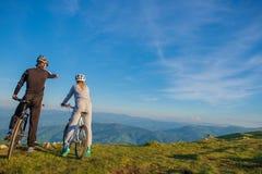 Пары велосипедиста при горный велосипед указывая в расстояние на сельскую местность Стоковая Фотография RF