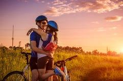 Пары велосипедистов обнимая после ехать в пригородах Активный здоровый образ жизни Молодые велосипедисты путешествуют совместно Стоковое Изображение RF