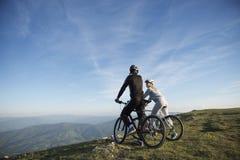 Пары велосипедиста при горные велосипеды стоя на холме под небом вечера и наслаждаясь ярким солнцем на заходе солнца Стоковые Изображения