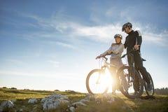 Пары велосипедиста при горные велосипеды стоя на холме под небом вечера и наслаждаясь ярким солнцем на заходе солнца Стоковые Изображения RF